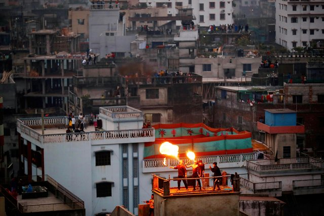 People perform fire breathing on their rooftop during Sakrain festival in Dhaka, Bangladesh on January 14, 2021. (Photo by Mohammad Ponir Hossain/Reuters)