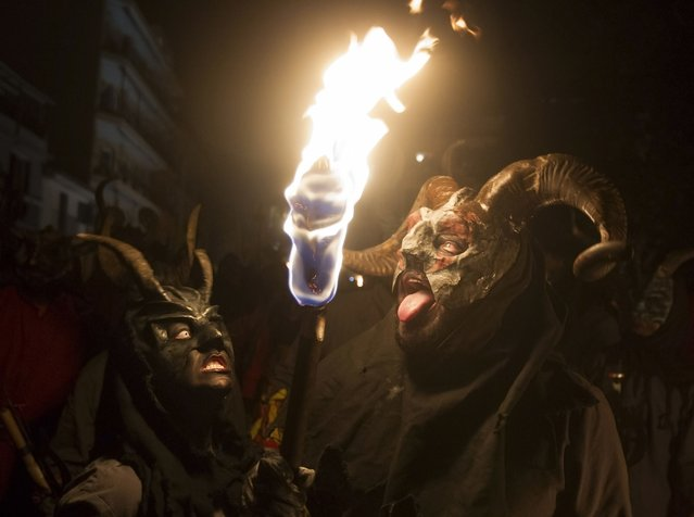 "Revellers wearing a demon costume take part in the traditional festival of ""Correfoc"" in Palma de Mallorca, on January 17, 2015. (Photo by Jaime Reina/AFP Photo)"