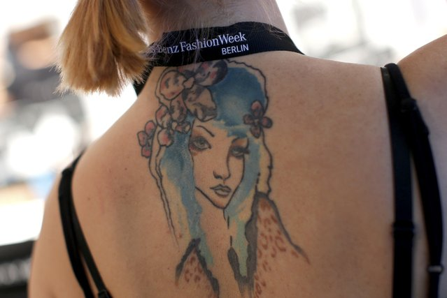 The tattoo of a make-up artist is pictured backstage before creations by Charlotte Ronson are presented at the Berlin Fashion Week Autumn/Winter 2015 in Berlin January 19, 2015. (Photo by Fabrizio Bensch/Reuters)