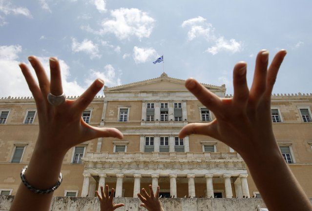 Protesters gesture in front of the Greek parliament during a rally against government austerity measures in  Athens in this June 29, 2010 file photo. (Photo by John Kolesidis/Reuters)