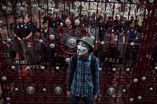 A protester wearing a Guy Fawkes mask, stand in front of a gate secured by Thai police officers as he and thousands of protesters gather in Bangkok's shopping district on June 23, 2013. Thousands of people marched through central Bangkok to protest against the former prime minister Thaksin Shinawatra and the current government led by his sister Thai Prime minister Yingluck Shinawatra. (Photo by Nicolas Asfouri/AFP Photo)