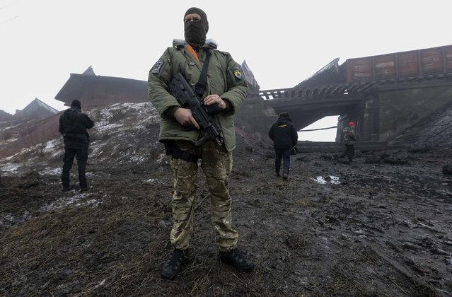 A Ukrainian serviceman guards as emergency workers inspect a damaged bridge near Kuznetsovka village in Zaporizhzhya region January 21, 2015. (Photo by Reuters/Stringer)