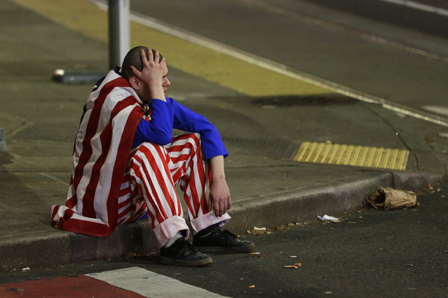 A man dressed in red-white-and-blue sits on the curb during a protest against President-elect Donald Trump, Wednesday, November 9, 2016, in Seattle's Capitol Hill neighborhood. (Photo by Ted S. Warren/AP Photo)