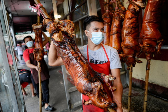 "Workers wearing face masks as a protection against the coronavirus disease (COVID-19) carry roasted pigs, locally known as ""lechon"", at a restaurant, in Quezon City, Metro Manila, Philippines, December 21, 2020. (Photo by Lisa Marie David/Reuters)"