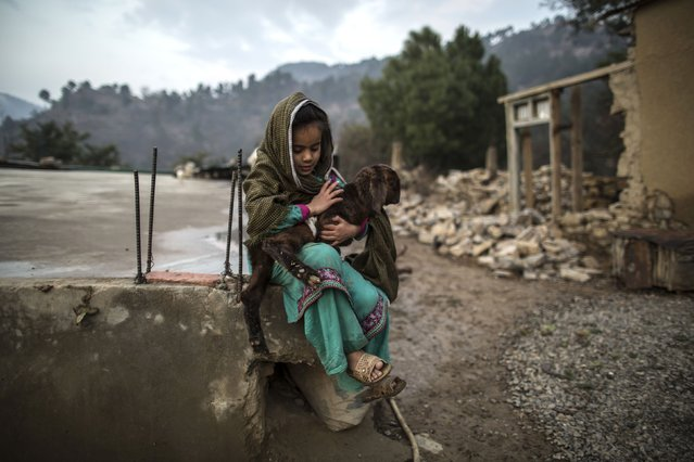 A girl holds a goat outside her house on Margalla Hills in Islamabad January 22, 2015. (Photo by Zohra Bensemra/Reuters)