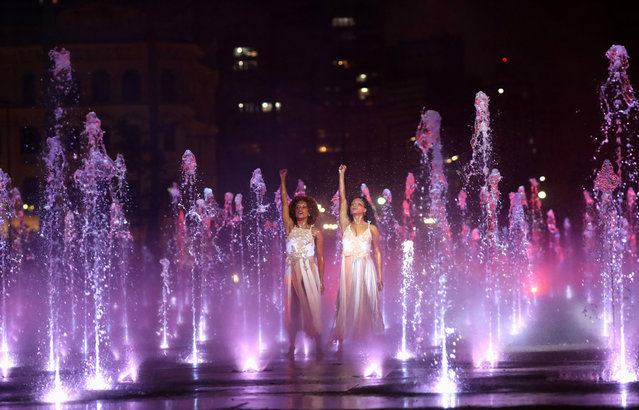 Dancers raise their fists at the end of a dance in the middle of a water fountain during a presentation to mark the opening of Sao Paulo Fashion Week as the event and creations are all presented online due to the outbreak of coronavirus disease (COVID-19) in Sao Paulo, Brazil on November 4, 2020. (Photo by Amanda Perobelli/Reuters)