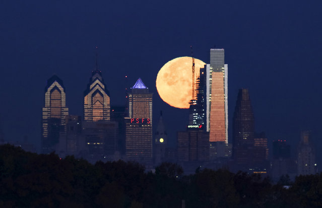 The supermoon sets behind the Philadelphia skyline on Monday, November 14, 2016. The brightest moon in almost 69 years lights up the sky this week in a treat for star watchers around the globe. The phenomenon is known as the supermoon. (Photo by Joseph Kaczmarek/AP Photo)