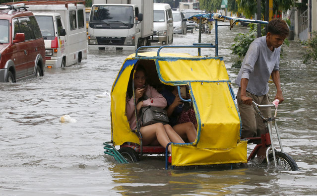 Commuters ride a pedicab, a pedaled tricycle, to go to work amidst flooding in a street in Manila after overnight Southwest monsoon rains brought about by tropical storm Ampil inundated low-lying areas in Metropolitan Manila and nearby provinces Friday, July 20, 2018 in Manila, Philippines. Heavy rains continue to flood Manila forcing authorities to suspend classes for the third straight day Friday. (Photo by Bullit Marquez/AP Photo)