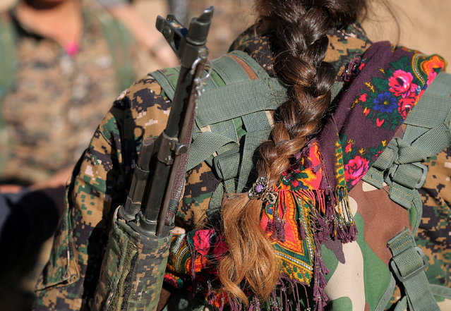 A Syrian Democratic Forces (SDF) female fighter's braid is pictured while she is carrying her weapon in Tal Samin village, north of Raqqa city, Syria November 19, 2016. (Photo by Rodi Said/Reuters)
