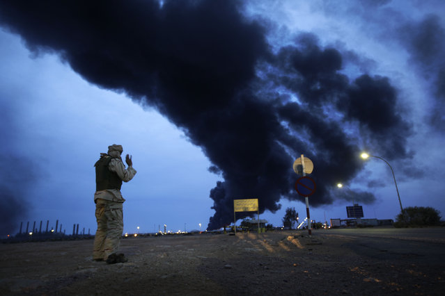 In this photo taken during a government-organised visit for foreign media, a pro-Gadhafi fighter makes his evening prayers in the desert as a plume of smoke rises from the burning oil refinery in Ras Lanouf, 380 miles (615 kilometers) southeast of the capital Tripoli, in Libya Saturday, March 12, 2011. (Photo by Ben Curtis/AP Photo)
