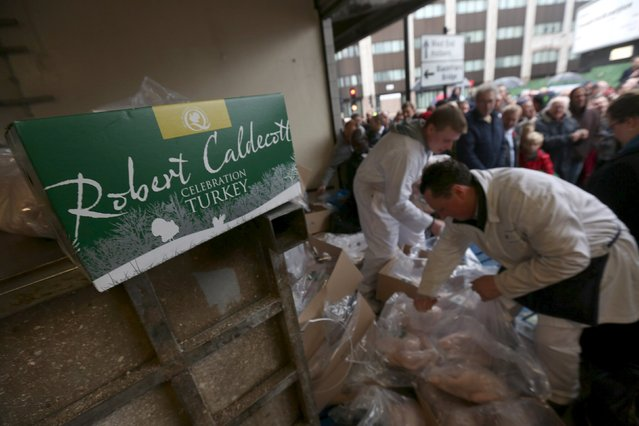 Butchers open boxes of turkey as they sell their remaining produce of the year at discounted prices during the traditional Christmas Eve auction at Smithfield's market in London December 24, 2015. (Photo by Neil Hall/Reuters)