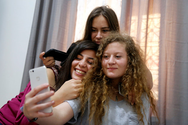 Ahed Tamimi takes a selfie with her friends at her family's house in Nabi Saleh village in the occupied West Bank July 30, 2018. The Palestinian teenager released by Israel on Sunday after completing a prison term for kicking and slapping an Israeli soldier said she wanted to become a lawyer so she could continue her struggle against the occupation of the West Bank. (Photo by Raneen Sawafta/Reuters)