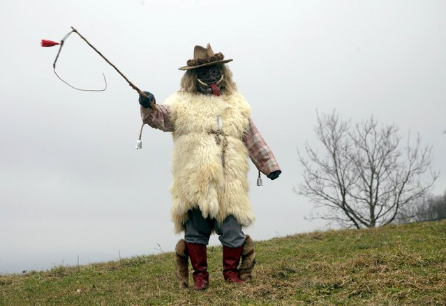 """A member of the Liski Pustje Ethnological Society dressed in a native mask and costume named """"Ramaston"""" poses ahead of the Carnival in Kanal ob Soci January 14, 2015. (Photo by Srdjan Zivulovic/Reuters)"""
