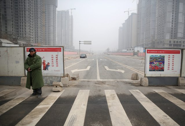 Construction sites are seen beside a newly-finished road in Xi'an, Shaanxi province, January 26, 2015. Steel demand in the world's biggest producer has also slowed as construction activities have been hampered by cold weather, further dampening prices. (Photo by Reuters/Stringer)