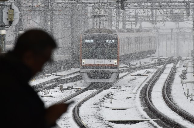 A train approaches a station in snowfall in Tokyo on November 24, 2016. (Photo by Kazuhiro Nogi/AFP Photo)