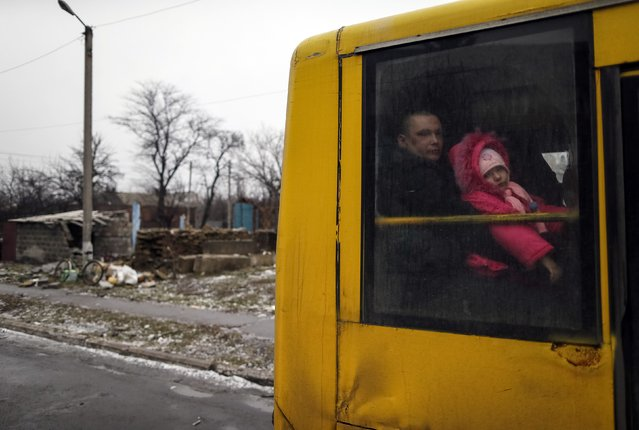 A man and a child look through a bus window before leaving as people flee the conflict in Debaltseve, eastern Ukraine, February 6, 2015. Convoys of buses converged from two sides on the town of Debaltseve in eastern Ukraine on Friday after separatist rebels and government forces appeared to have patched together a truce to allow civilians to be evacuated. (Photo by Gleb Garanich/Reuters)