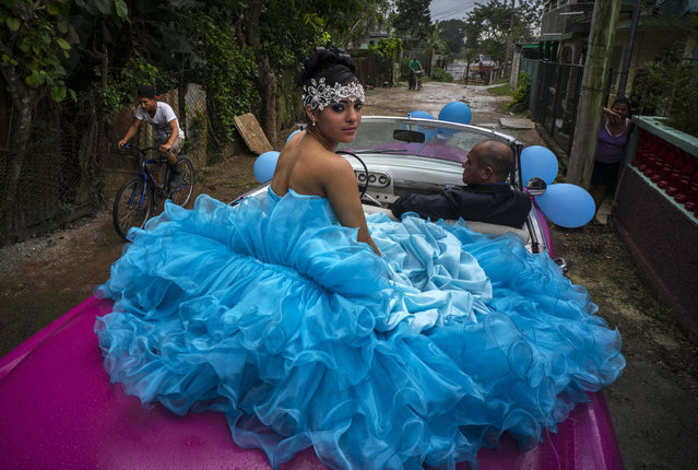 In this December 20, 2015 photo, Daniela Santos Torres, 15, waits in a classic American car with her father Ivan Santos to ride to her quinceanera party in the town of Punta Brava near Havana, Cuba. (Photo by Ramon Espinosa/AP Photo)