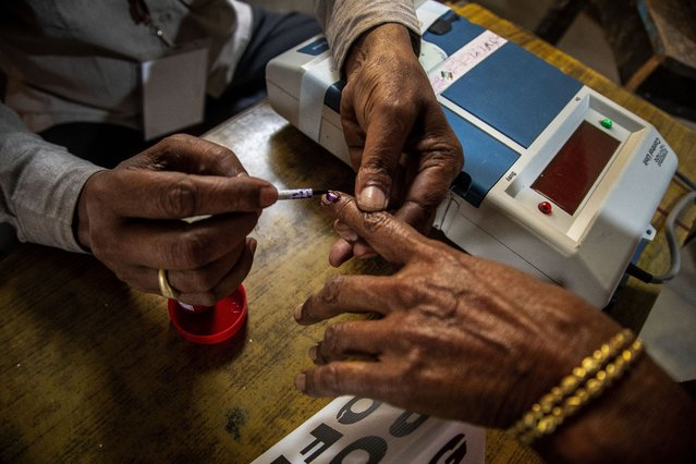 A polling officer applies indelible ink on a voter's finger at a polling station during the third phase of assembly election in Gauhati, India, Tuesday, April 6, 2021. (Photo by Anupam Nath/AP Photo)