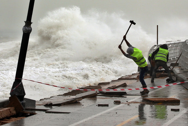 Municipal workers remove broken tiles near the fence of Beirut's seaside corniche which was damaged by strong and high waves in Lebanon, Wednesday, February 11, 2015. The Middle East is being hit with a storm that has brought heavy winds, rain and snow to Lebanon's mountains. Lebanon's weather authorities said the wind was at a speed of 100 kilometers (60 miles) per hour. (Photo by Hussein Malla/AP Photo)