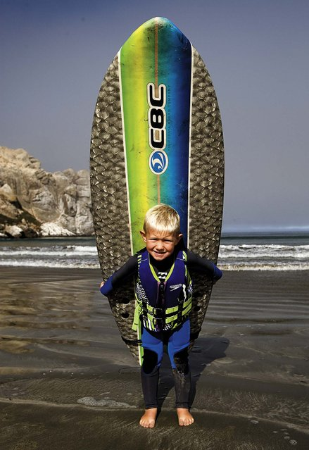 Triston poses for a photo with his surfboard before catching some waves with his father. (Photo by Joe Johnston/The Tribune of San Luis Obispo)
