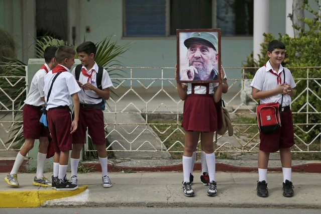 Children stand along a street while waiting for the ashes of Fidel Castro to pass during a three-day journey to the eastern city of Santago, in Cardenas, Cuba, November 30, 2016. (Photo by Enrique De La Osa/Reuters)