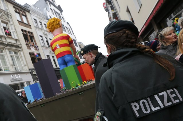 Police and carnival revellers stand in front of a carnival float carrying papier-mache figures depicting Charlie Hebdo, during the traditional Rose Monday carnival parade in Cologne February 16, 2015. (Photo by Wolfgang Rattay/Reuters)