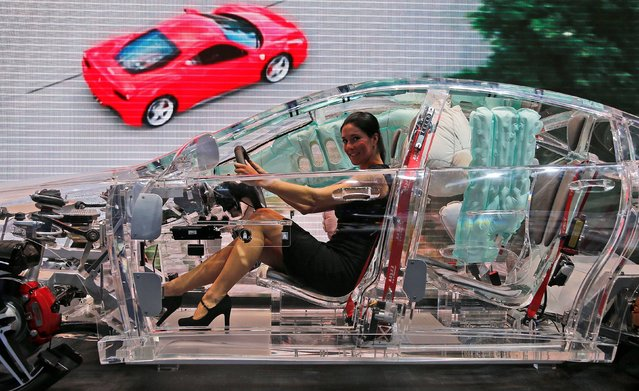 A woman sits in a car made of glass on display at the TRW booth, a worldwide leader in car protections systems, during the second press day of the 65th Frankfurt Auto Show in Frankfurt, Germany, Wednesday, September 11, 2013. More than 1,000 exhibitors will show their products to the public from September 12 through September 22, 2013. (Photo by Frank Augstein/AP Photo)