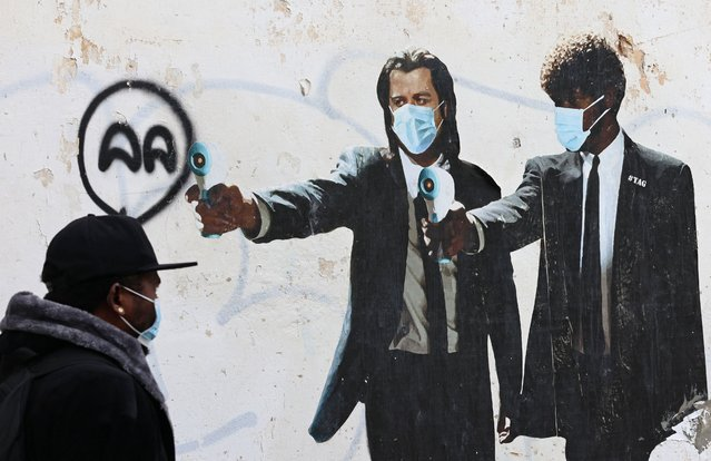 A man walks past a mural depicting US actors John Travolta and Samuel L. Jackson holding thermometers instead of guns amid the Covid-19 pandemic, in Tel Aviv on March 1, 2021. (Photo by Emmanuel Dunand/AFP Photo)