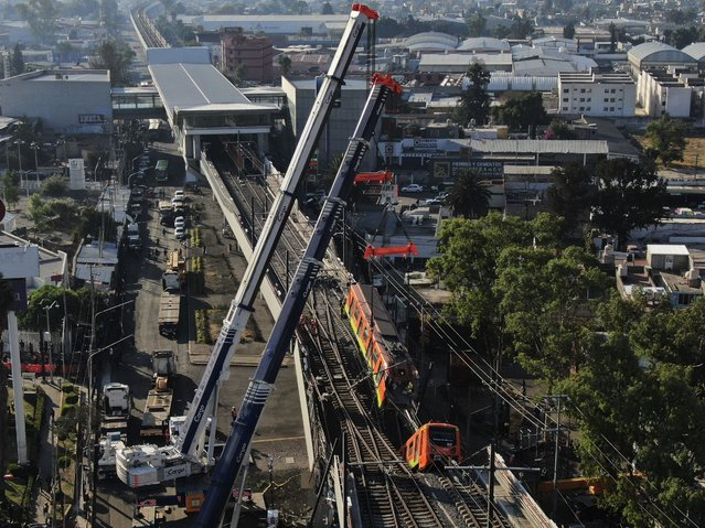 Subway cars dangle at an angle from a collapsed elevated section of the metro, in Mexico City, Tuesday, May 4, 2021. The elevated section of the metro's Line 12 collapsed late Monday killing at least 23 people and injuring at least 79, city officials said. (Photo by Fernando Llano/AP Photo)