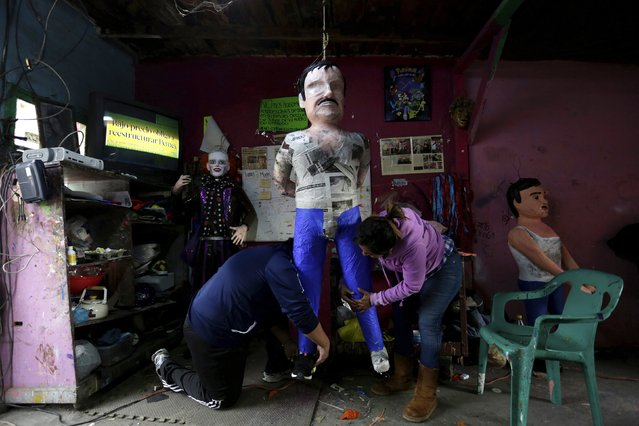 """Artisans work on a pinata depicting the drug lord Joaquin """"El Chapo"""" Guzman at a workshop in Reynosa, in Tamaulipas state, Mexico, January 13, 2016. (Photo by Daniel Becerril/Reuters)"""
