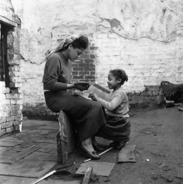 A young woman and young girl in the yard of their house in Sophia Street, Bute Town, one of the poorest areas in Cardiff, 23rd January 1954. The area has a lively ethnic mix of families with Arab, Somali, West African, West Indian, Egyptian, Greek, and many other origins. (Photo by Bert Hardy/Picture Post/Getty Images)