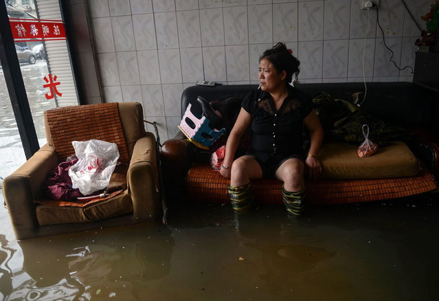 In this photo provided by China's Xinhua News Agency, a woman rests as she sits in a flooded building in Cangnan County, east China's Zhejiang Province, Monday, October 7, 2013. Five people have been reported killed as a typhoon hit southeastern China on Monday with powerful winds and heavy rains causing widespread damage. (Photo by AP Photo/Xinhua News Agency)