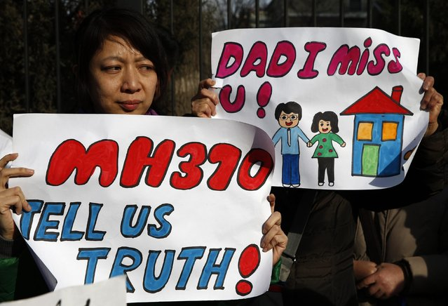Catherine Gang, whose husband Li Zhi was onboard the missing Malaysia Airlines flight MH370, holds a sign during a gathering of family members of the missing passengers outside the Malaysian embassy in Beijing March 8, 2015. Malaysian and Chinese officials say they are committed to the search for MH370 and in assisting families who are still waiting for concrete information on what happened to their loved ones a year ago.