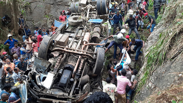 Sri Lankan police officers and rescuers lift out the body of a survivor from the debris of a bus that plunged into a precipice in Passara, about 240 kilometers east of Colombo, Sri Lanka, Saturday, March 20, 2021. A passenger bus plunged off a road in central Sri Lanka on Saturday, killing more than a dozen people and injuring more than 30. (Photo by Prasanna Pathmasiri/AP Photo)