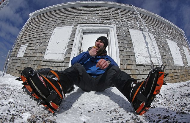 In this Tuesday, March 10, 2015 photo, Nathan Iannuccillo, 23 of Smithfield, R.I., takes a lunch break after climbing more than 4 miles to reach the summit of Mount Washington, New Hampshire. Sharp steel crampons give him traction on the icy trails. (Photo by Robert F. Bukaty/AP Photo)