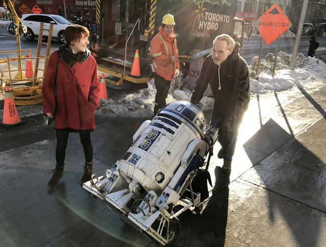 "Steven Schwarzentruber (R), a member of the R2 builders club, wheels his replica ""R2E6"" home after attending a Star Wars-themed benefit at a Cineplex for the Daily Bread food bank in Toronto, Ontario, Canada December 19, 2016. (Photo by Chris Helgren/Reuters)"