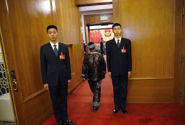 A minority delegate (C) in traditional costume walks past security personnel as he arrives before the third plenary meeting of the National People's Congress, China's parliament, at the Great Hall of the People, in Beijing, March 12, 2015. (Photo by Kim Kyung-Hoon/Reuters)