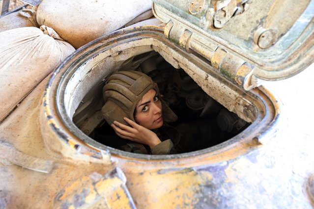 A female Syrian soldier from the Republican Guard commando battalion drives a tank during clashes with rebels in the restive Jobar area, in eastern Damascus, on March 25, 2015. The female battalion, which was created nearly a year ago, consists of 800 female soldiers who are positioned in the suburbs of the Syrian capital where they monitor and secure the frontlines with snipers, rockets and machine guns. (Photo by Joseph Eid/AFP Photo)