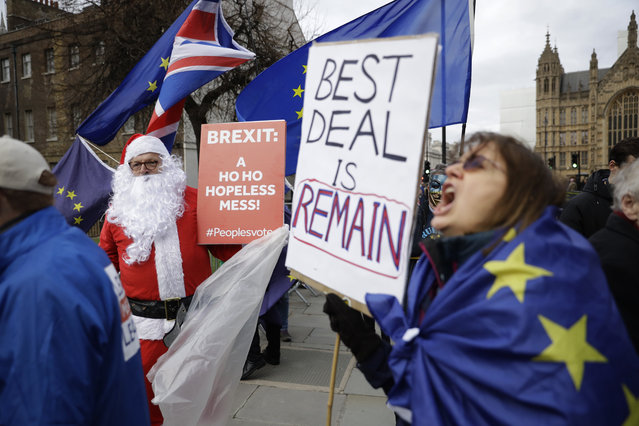 Remaining in the European Union supporters, including one dressed as Santa, hold placards and protest outside the Houses of Parliament in London, Monday, December 10, 2018. British Prime Minister Theresa May looked set Monday to postpone Parliament's vote on her European Union divorce deal to avoid a shattering defeat, throwing Brexit plans into chaos just weeks after Britain and the bloc finally reached an agreement on the U.K.'s departure. (Photo by Matt Dunham/AP Photo)