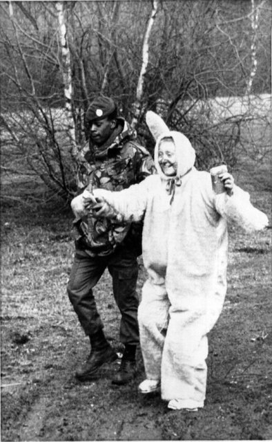 April 1, 1983 A peace Campaigner, dressed as an Easter bunny, being escorted by a member of the Royal Air Force Regiment inside Greenham Common air base Friday after about 40 demonstrators scaled the fending at the proposed Cruise missile site on the second day of an Easter Protest. (Photo by  AP Wirephoto)