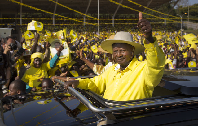 Uganda's long-time President Yoweri Museveni waves to supporters from the sunroof of his vehicle as he arrives for an election rally at Kololo Airstrip in Kampala, Uganda Tuesday, February 16, 2016. Opposition leader Kizza Besigye, in a close race with Museveni, said Tuesday he does not believe the election will be free and fair. (Photo by Ben Curtis/AP Photo)