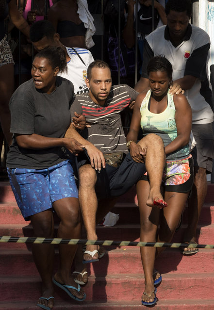 Women carry a man with a bleeding foot away from the building they invaded about a week ago as police evict them, in the Flamengo neighborhood of Rio de Janeiro, Brazil, Tuesday, April 14, 2015. (Photo by Silvia Izquierdo/AP Photo)