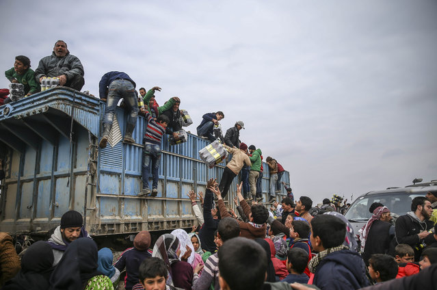 Turkish humanitarian aid organization members distribute humanitarian aids for Syrians, who fled bombing in Aleppo at a tent city close to the Bab al-Salam border crossing on Turkish-Syrian border near Azaz town of Aleppo, Syria on February 13, 2016. Russian airstrikes have recently forced some 40,000 people to flee their homes in Syrias northern city of Aleppo. (Photo by Fatih Aktas/Anadolu Agency/Getty Images)