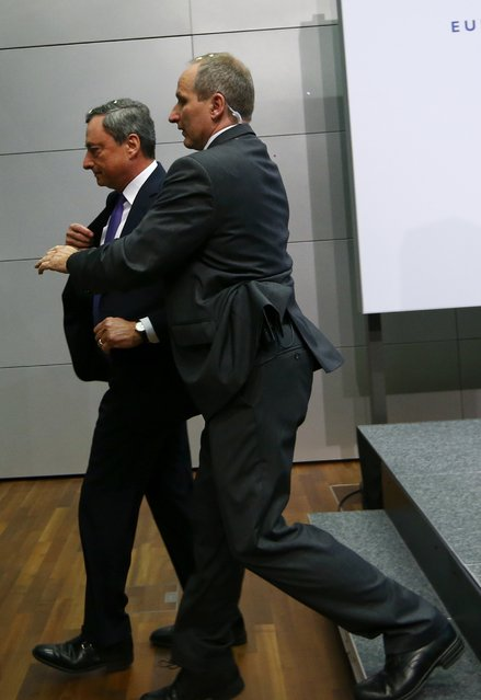A  security officer leads European Central Bank President Mario Draghi away from the room during a news conference in Frankfurt, April 15, 2015. (Photo by Ralph Orlowski/Reuters)