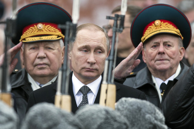 Russian President Vladimir Putin, center, attend a wreath-laying ceremony at the Tomb of the Unknown Soldier in Moscow, Russia, Tuesday, Feb. 23, 2016. The Defenders of the Fatherland Day, celebrated in Russia on February 23, honors the nation's military and is a nationwide holiday. (Photo by Pavel Golovkin/AP Photo)