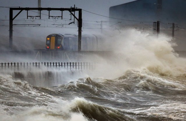 A train passes through the coast at Saltcoats in Scotland, January 3, 2014, as Britain is braced for the worst as a combination of high tides, heavy rains and strong winds are expected to bring yet more severe flooding to parts of the country. (Photo by Danny Lawson/PA Wire)