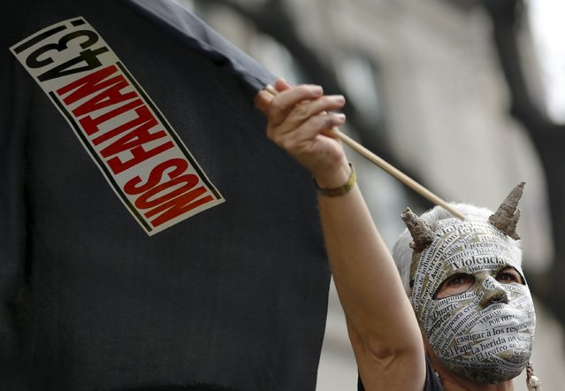 """An activist holds up a flag with a poster as she takes part in a demonstration to mark the 17-month anniversary of the disappearance of the 43 missing students of Ayotzinapa College Raul Isidro Burgos, outside the Supreme Court building in Mexico City, Mexico February 26, 2016. The students disappeared on the night of September 26, 2014 in the southwestern city of Iguala. The words reads, """"We are missing 43"""". (Photo by Henry Romero/Reuters)"""