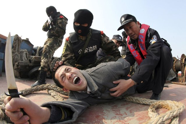 """Paramilitary policemen and police officers """"arrest"""" a man acting as an attacker with a knife during an anti-terrorism drill in Rugao, on January 6, 2014. (Photo by Reuters/Stringer)"""