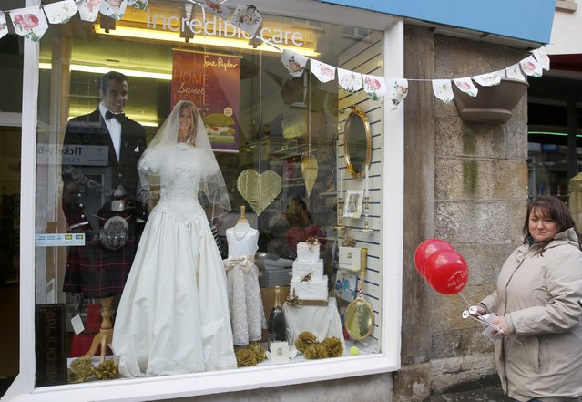 A shop window is decorated with a wedding dress and men's formal wear with the faces of tennis player Andy Murray and his fiancee Kim Sears in Dunblane, Scotland, April 11, 2015. (Photo by Russell Cheyne/Reuters)
