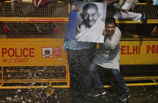 A supporter of the youth wing of India's opposition Congress Party hold a portrait of Mahatma Gandhi as police use water canons to stop protesters from marching towards Indian Parliament during a protest in New Delhi, India, Wednesday, March 2, 2016. The protest was against a statement given by Smriti Irani, India's Human Resource Development Minister, in the Indian Parliament during a debate on recent student protests in the country. (Photo by Altaf Qadri/AP Photo)